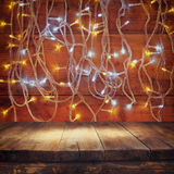 Wood board table in front of Christmas warm gold garland lights on wooden rustic background. filtered image. selective focus Royalty Free Stock Image