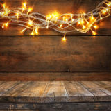 Wood board table in front of Christmas warm gold garland lights on wooden rustic background. filtered image. selective focus royalty free stock photo