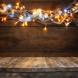 Wood board table in front of Christmas warm gold garland lights on wooden rustic background. filtered image. selective focus