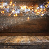 Wood board table in front of Christmas warm gold garland lights on wooden rustic background. filtered image. selective focus. Royalty Free Stock Photo