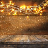 Wood board table in front of Christmas warm gold garland lights on wooden rustic background. filtered image. selective focus. Glitter overlay Stock Image