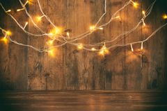 Wood board table in front of Christmas warm gold garland lights on wooden rustic background. glitter overlay.  royalty free stock photo