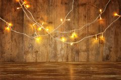 Wood board table in front of Christmas warm gold garland lights on wooden rustic background. glitter overlay Royalty Free Stock Image