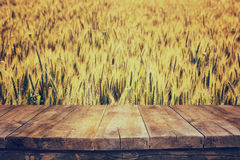 Wood board table in front of field of wheat on sunset light. Ready for product display montages Stock Images