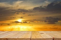 wood board table in front of golden sunset. product display background. stock image