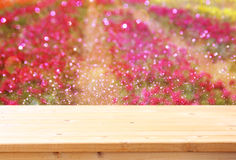 Wood board table in front of summer landscape of field with many flowers Stock Image