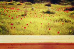 Wood board table in front of summer landscape of field with many flowers . background is blurred Stock Image