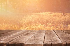Wood board table in front of summer landscape with lens flare. Stock Photo