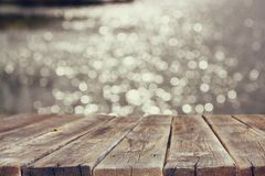 Wood board table in front of summer landscape of sparkling lake water. background is blurred.  Stock Photography