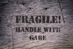 Fragile Handle with Care on wooden texture. Wood board with warning label stencil using back paint outside Royalty Free Stock Photography