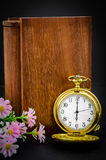Wood book cover with golden pocket watch. Wood book cover with golden pocket watch on black background Royalty Free Stock Photo
