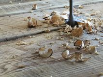 Wood boring bit shavings. Paddle bit drilling hole through wood with curly wood shavings Stock Image