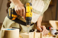 Wood boring drill in hand drilling hole in wooden bar Royalty Free Stock Photography