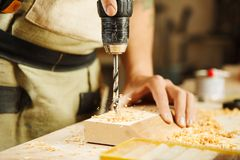 Wood boring drill in hand drilling hole in wooden bar Stock Photo