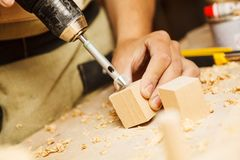 Wood boring drill in hand drilling hole in wooden bar Royalty Free Stock Image