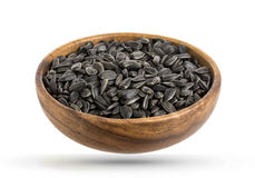 Wood bowl of black sunflower seeds isolated on white background Stock Photos