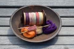 Wood bowl filled with a spinning wheel bobbin of hand spun yarn, fiber, and a knitted sample Stock Photography
