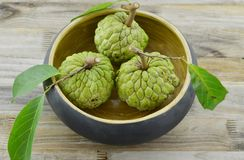 Wood-bowl with new harvest custard apple on wooden background stock photos
