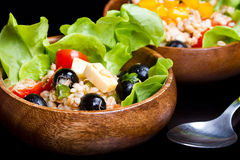 Wood bowl with spelt salad with olives and tomatoes Stock Photos