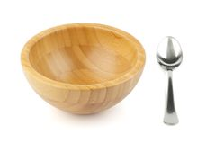 Wood bowl and steel spoon Royalty Free Stock Image