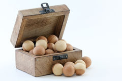 Wood Box and Cedar Balls. Wood box filled with smooth cedar balls used as moth and insect repellent; white background Royalty Free Stock Photography