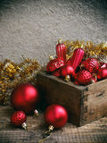 Wood box with red Christmas decorations. New Year and Xmas card background. Copy space. Selective focus. Royalty Free Stock Images