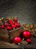 Wood box with red Christmas decorations. New Year and Xmas card background. Copy space. Selective focus. Stock Photos