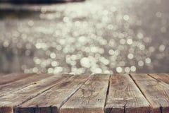 Wood brädetabell framme av sommarlandskapet av mousserande sjövatten Bakgrund är suddig Arkivbild