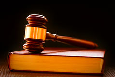 Wood and brass judges gavel on a law book Stock Image
