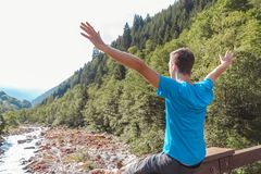 Man`s arms raised on a bridge crossing a river surrounded by mountains royalty free stock photography