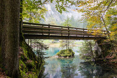Wood bridge over the green water lake Stock Photos