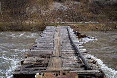 Wood bridge over a mountain river. A small bridge across a rushing mountain river in the high water period Royalty Free Stock Photography