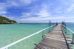 Wood bridge pier on summer tropical sea in blue sky. Stock Images