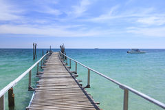 Wood bridge pier on summer tropical sea in blue sky. Royalty Free Stock Image