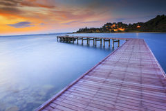 Wood bridge piers with nobody and smoothy sea water against beau. Tiful sun rising sky Royalty Free Stock Photos