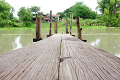 Wood bridge into the river Stock Photography
