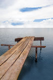 Wood bridge under the sky at an ocean. royalty free stock photos