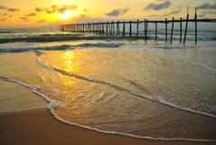 Wood bro med solnedgångstranden Arkivbild