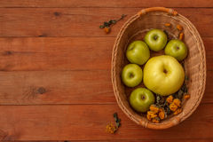 Wood brown background with a basket of green apples. Wood brown background with a basket green and yellow apples Royalty Free Stock Images