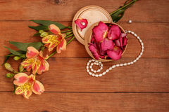Wood brown background with orange Alstromeria and rose petals. Wood plank brown background with orange Alstroemeria ,rose petals in round box and necklace of Royalty Free Stock Images