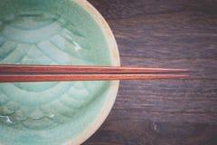 Wood brown chopsticks and celadon green ceramic Stock Photography