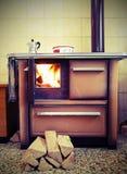 wood-burning火炉在瑞士山中的牧人小屋的厨房里与老被定调子的作用的 库存图片