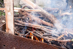 Wood burning in a barbeque grill. Closeup of firewood Stock Photos