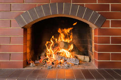 Wood burning fireplace in a bright fire. Firewood burn bright fire in the fireplace Stock Images