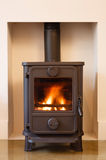Wood burning stove. Cast iron wood burning stove in a modern contemporary fireplace Royalty Free Stock Photo