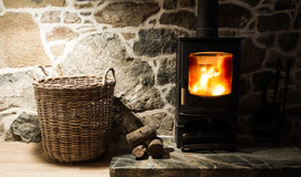 Wood Burning Stove and Fireplace. The interior of a stone walled cottage showing the hearth and fireplace with a wood burning stove that is glowing with flames Royalty Free Stock Image