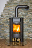 Wood burning stove in house. Roaring fire inside wood burning stove in living room Royalty Free Stock Photography