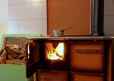 Wood burning stove in a kitchen of a mountain home with a pot on Stock Photography