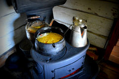 Wood Burning Stove. An old fashioned cast iron wood burning stove with two kettles and a pot of chicken dumpling soup cooking on the stovetop. This was taken at Stock Photo