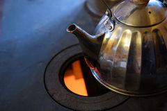 Wood burning stove. Tea is on the stove plate. royalty free stock images